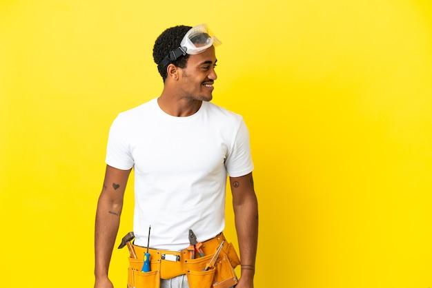 Elettricista afroamericano sopra il muro giallo isolato che guarda di lato e sorride