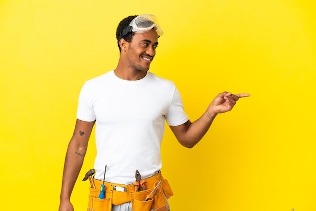 Elettricista afroamericano sopra il muro giallo isolato che punta il dito sul lato e presenta un prodotto
