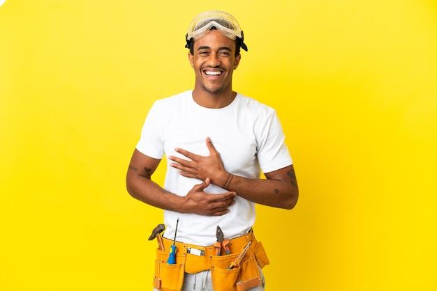 Elettricista afroamericano sopra il muro giallo isolato che sorride molto