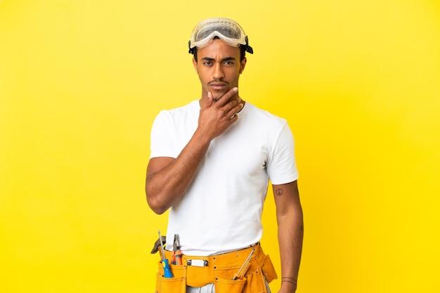 Uomo dell'elettricista afroamericano sopra il pensiero giallo isolato della parete