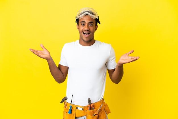 Elettricista afroamericano sopra il muro giallo isolato con espressione facciale scioccata