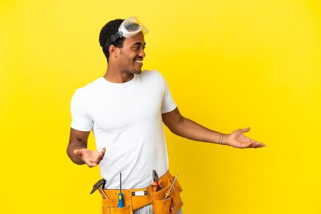 Elettricista afroamericano sopra il muro giallo isolato con espressione di sorpresa mentre guarda di lato