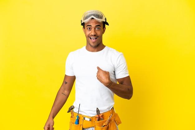 Elettricista afroamericano sopra il muro giallo isolato con espressione facciale a sorpresa
