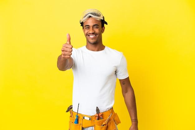Elettricista afroamericano sopra il muro giallo isolato con il pollice in alto perché è successo qualcosa di buono