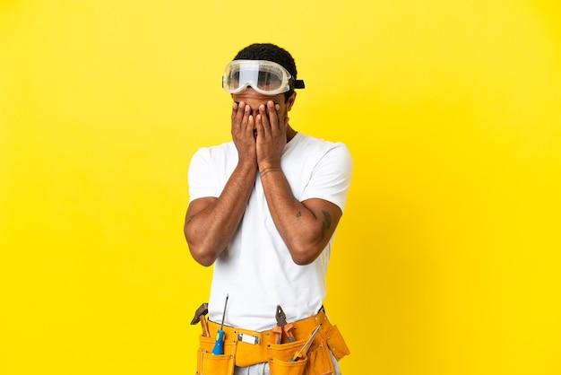 Elettricista afroamericano sopra il muro giallo isolato con espressione stanca e malata