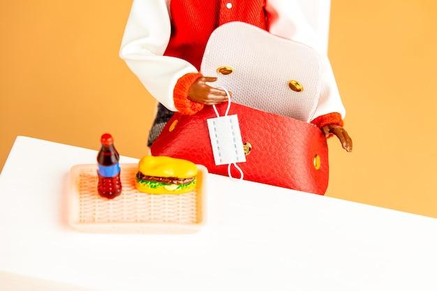 Maschera da tenere in mano con bambola femminile afroamericana accanto a un fast food su un tavolo