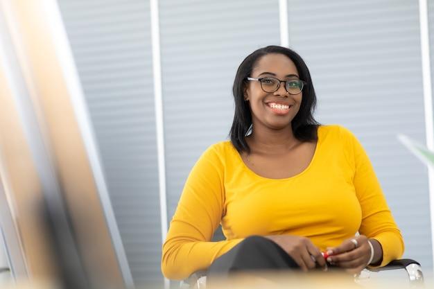 Relatore femminile afroamericano che indica la presentazione della lavagna a diversi dipendenti in riunione presso un ufficio moderno