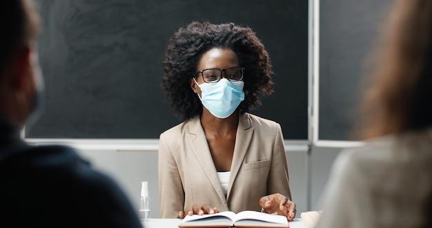 Insegnante femminile afroamericano in occhiali e mascherina medica che si siede al tavolo a scuola in classe, leggendo libri di testo e insegnando. lezione di letteratura. educatore donna che fa domande a studenti o alunni