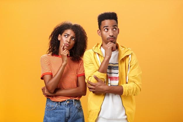 Amici afroamericani in abito urbano elegante in piedi in atteggiamento pensieroso