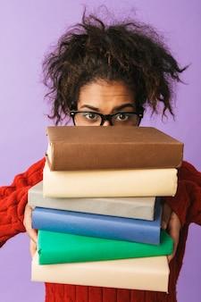 Ragazza divertente afroamericana in uniforme scolastica che tiene mazzo di libri, isolata