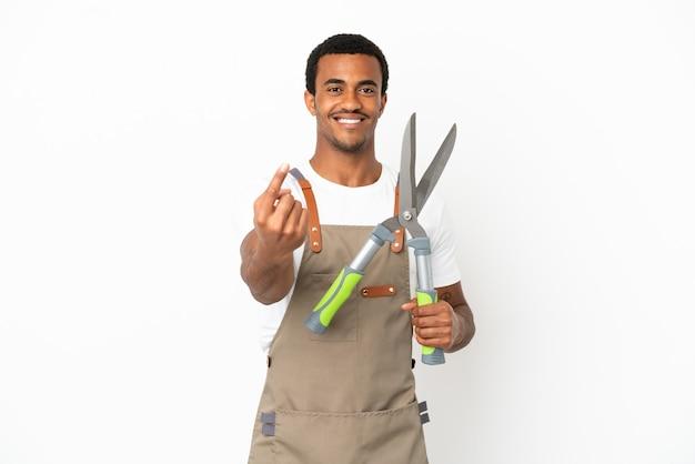 Giardiniere afroamericano uomo con forbici da potatura su sfondo bianco isolato facendo gesto imminente