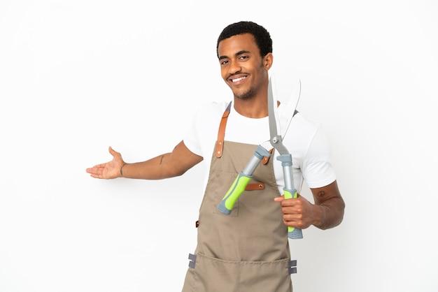 Giardiniere afroamericano uomo con forbici da potatura su sfondo bianco isolato estendendo le mani di lato per invitare a venire