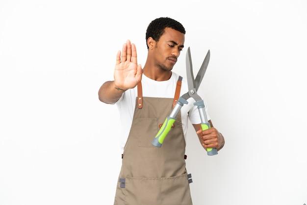 Giardiniere afroamericano uomo con forbici da potatura su sfondo bianco isolato facendo gesto di arresto e deluso