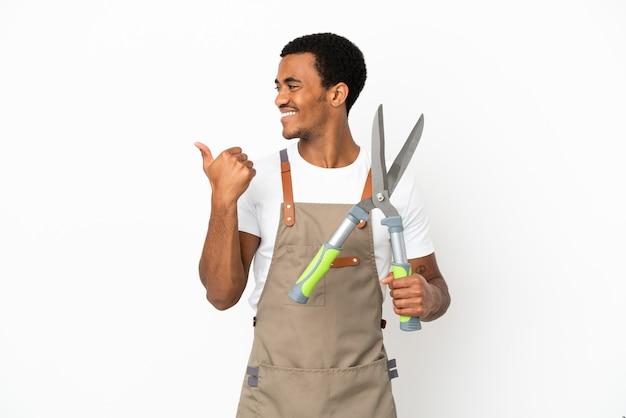 Giardiniere afroamericano uomo con forbici da potatura su sfondo bianco isolato rivolto verso il lato per presentare un prodotto