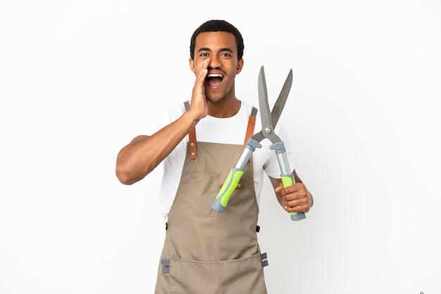 Uomo afroamericano giardiniere che tiene cesoie da potatura su sfondo bianco isolato che grida con la bocca spalancata