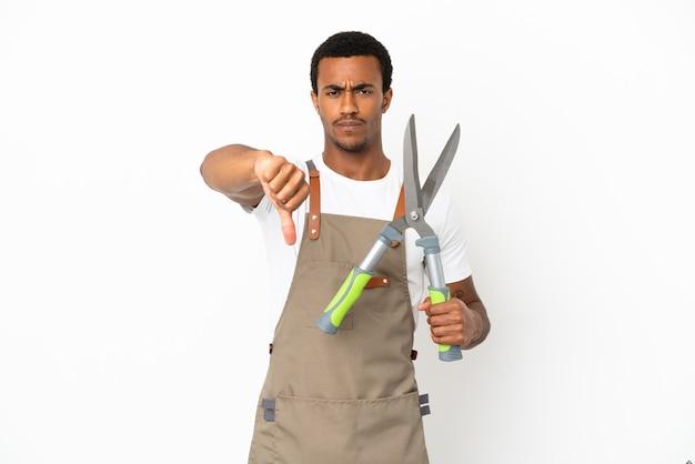 Giardiniere afroamericano che tiene le forbici da potatura su sfondo bianco isolato che mostra il pollice verso il basso con espressione negativa
