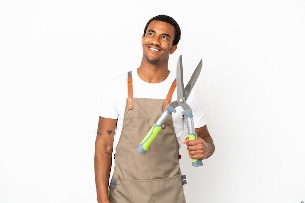 Giardiniere afroamericano uomo con forbici da potatura su sfondo bianco isolato pensando a un'idea mentre guarda in alto
