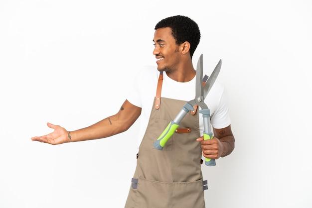Uomo afroamericano giardiniere che tiene forbici da potatura su sfondo bianco isolato con espressione di sorpresa mentre guarda di lato