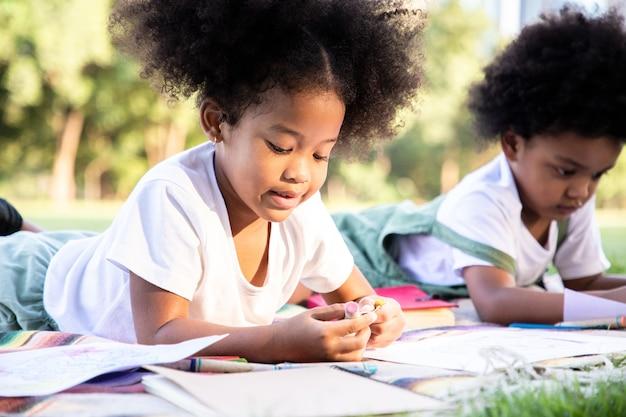 Ragazzo e una ragazza afroamericana stanno disegnando e dipingendo nel parco. usano la loro immaginazione e creatività nell'arte imparare idee fuori dalla classe
