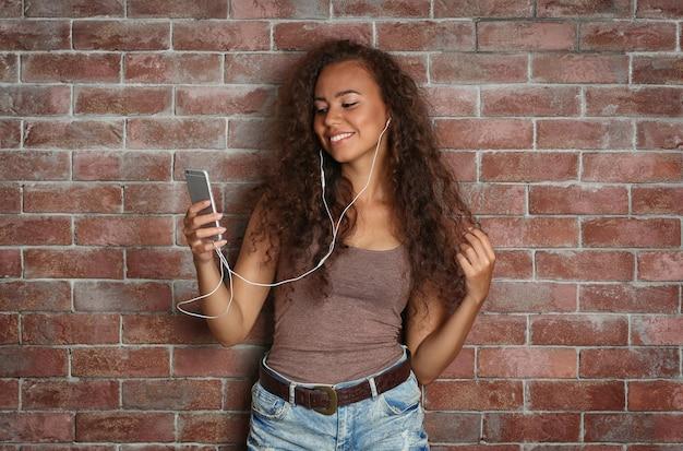 Musica d'ascolto della ragazza dell'afroamericano sul muro di mattoni