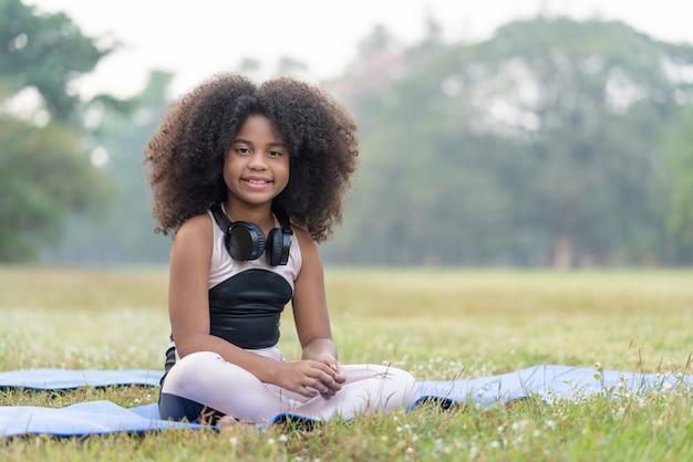 La ragazza afroamericana sorride e si siede su un materassino pratica lo yoga di meditazione nel parco all'aperto