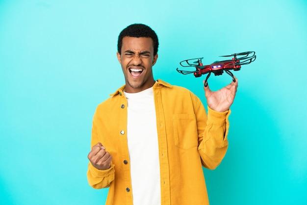 Bell'uomo afroamericano che tiene in mano un drone su sfondo blu isolato che celebra una vittoria