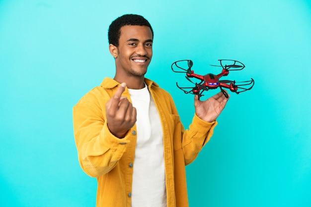 Bell'uomo afroamericano che tiene in mano un drone su sfondo blu isolato che fa un gesto imminente
