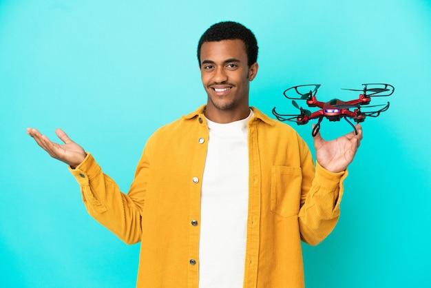 Bell'uomo afroamericano che tiene un drone su sfondo blu isolato che estende le mani di lato per invitare a venire