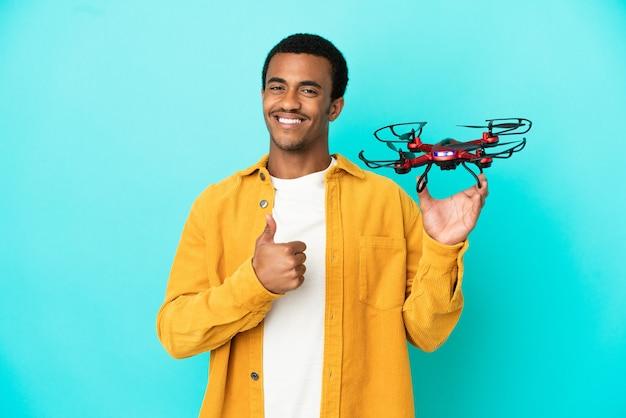 Bell'uomo afroamericano che tiene in mano un drone su sfondo blu isolato che fa un gesto di pollice in alto