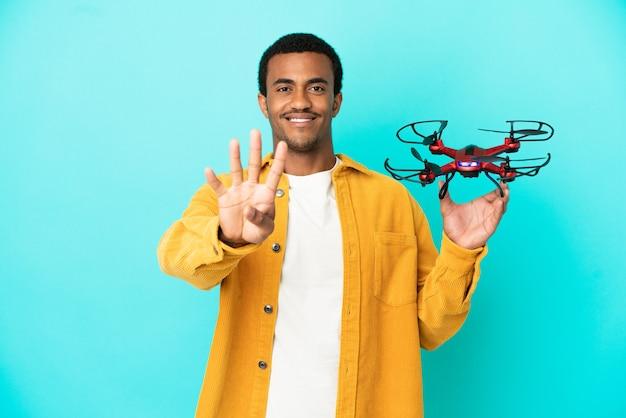 Uomo bello afroamericano che tiene un drone su sfondo blu isolato felice e conta quattro con le dita