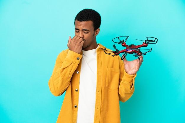 Uomo bello afroamericano che tiene un drone su sfondo blu isolato avendo dubbi