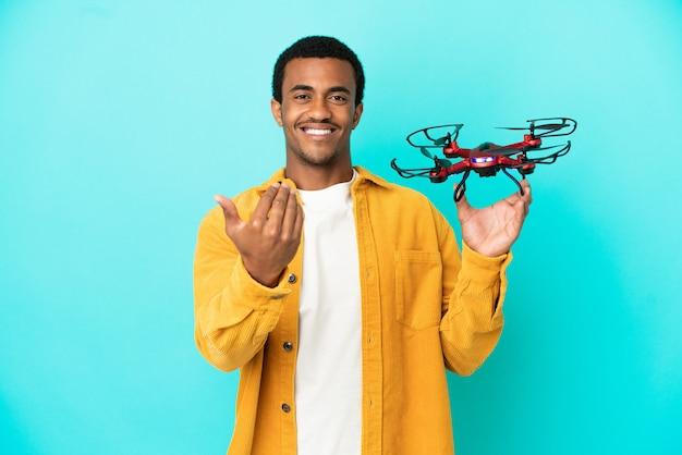 Uomo bello afroamericano che tiene un drone su sfondo blu isolato che invita a venire con la mano. felice che tu sia venuto