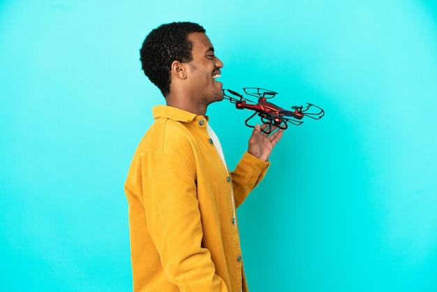 Bell'uomo afroamericano che tiene in mano un drone su sfondo blu isolato che ride in posizione laterale