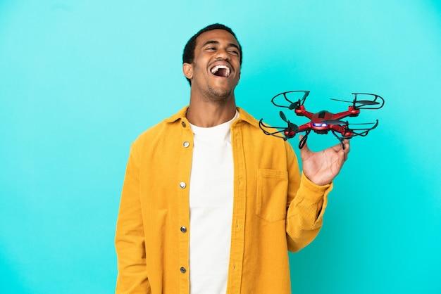 Bell'uomo afroamericano che tiene in mano un drone su sfondo blu isolato ridendo