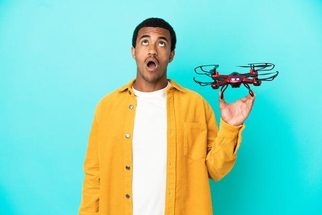Bell'uomo afroamericano che tiene in mano un drone su sfondo blu isolato guardando in alto e con espressione sorpresa