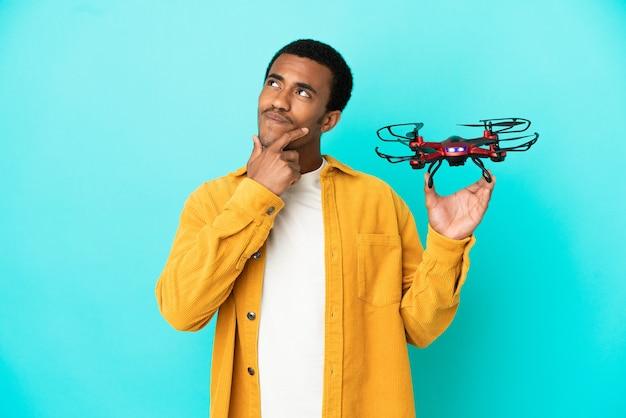 Bell'uomo afroamericano che tiene in mano un drone su sfondo blu isolato e guarda in alto