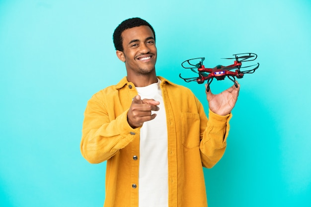 Uomo bello afroamericano che tiene un drone su sfondo blu isolato che punta davanti con espressione felice
