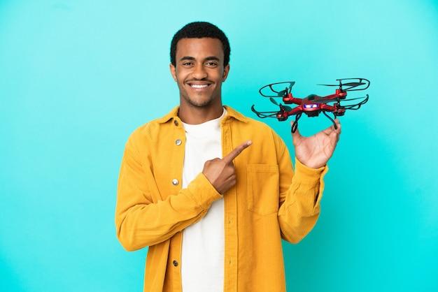 Bell'uomo afroamericano che tiene in mano un drone su sfondo blu isolato che punta al lato per presentare un prodotto