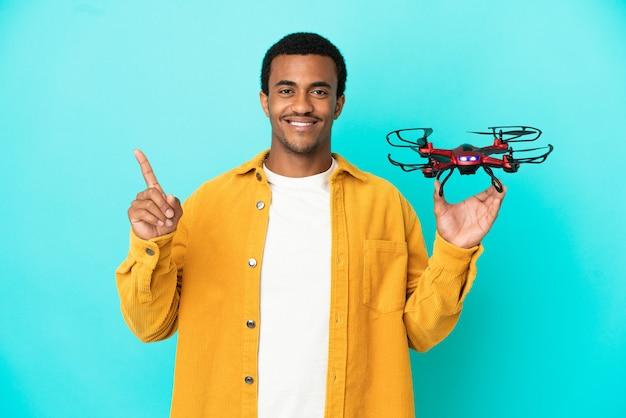 Uomo bello afroamericano che tiene un drone su sfondo blu isolato che punta su una grande idea