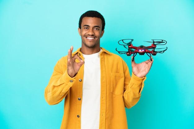 Bell'uomo afroamericano che tiene un drone su sfondo blu isolato che mostra segno ok con le dita