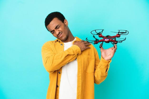 Bell'uomo afroamericano che tiene in mano un drone su sfondo blu isolato che soffre di dolore alla spalla per aver fatto uno sforzo