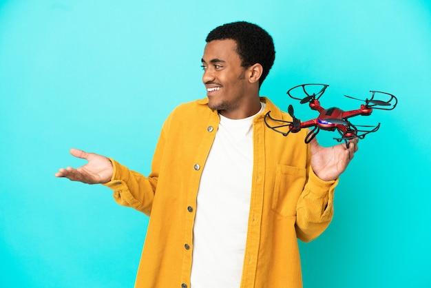 Bell'uomo afroamericano che tiene in mano un drone su sfondo blu isolato con espressione di sorpresa mentre guarda di lato