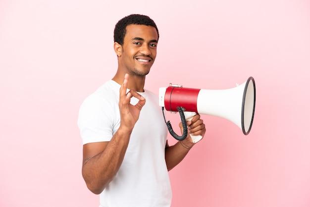 Bell'uomo afroamericano su sfondo rosa isolato che tiene in mano un megafono e mostra il segno ok con le dita