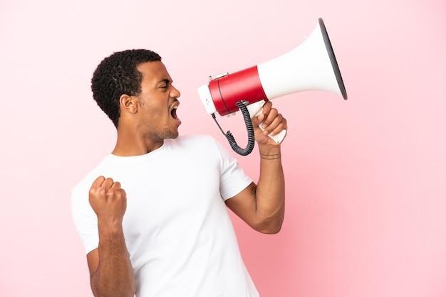 Bell'uomo afroamericano su sfondo rosa isolato che grida attraverso un megafono per annunciare qualcosa in posizione laterale