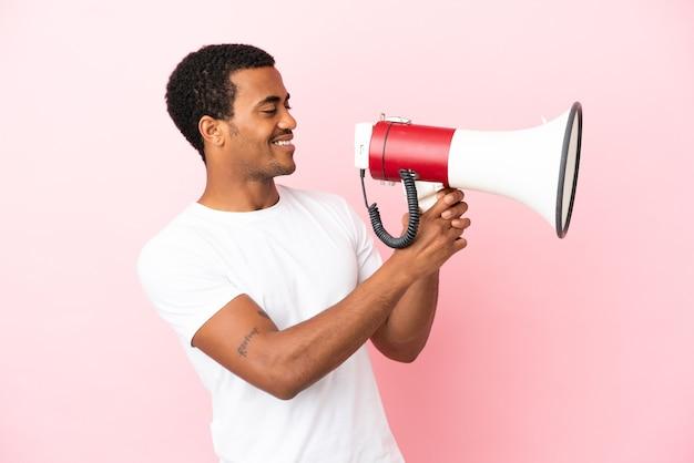 Bell'uomo afroamericano su sfondo rosa isolato che grida attraverso un megafono per annunciare qualcosa