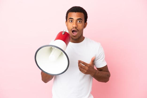 Bell'uomo afroamericano su sfondo rosa isolato che grida attraverso un megafono con espressione sorpresa