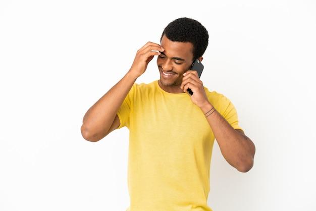 Bell'uomo afroamericano che usa il telefono cellulare su sfondo bianco isolato ridendo