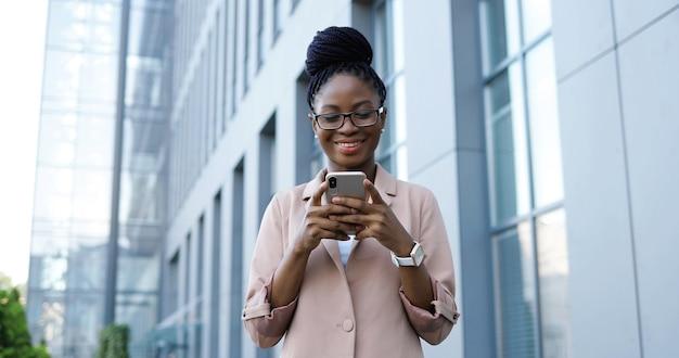 Giovane imprenditrice felice afroamericana toccando e scorrendo sullo smartphone. messaggio di sms di donna sul telefono cellulare all'aperto. femmina che utilizza gadget e sorride mentre chiacchiera.