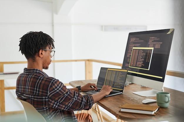 Sviluppatore it afro-americano che digita sulla tastiera con codice di programmazione nero e arancione sullo schermo del computer e laptop nell'interiore dell'ufficio contemporaneo, spazio della copia