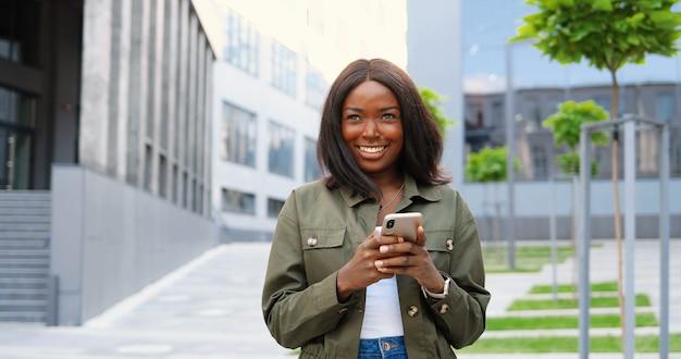Giovane donna alla moda gioiosa afroamericana toccando o scorrendo sullo smartphone e in piedi in via della città. bella felice messaggio di testo femminile sul cellulare e sorridente. al di fuori.